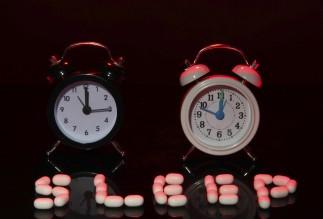Old style alarm clocks and pills, on dark background