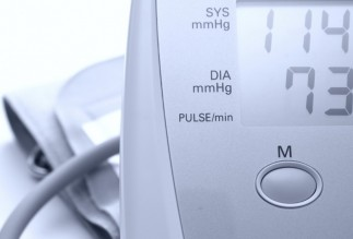 Detail of a digital blood pressure and heart rate monitor with arm band. Blue-tinted monochrome image