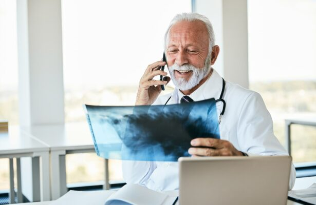 Doctor looking at X-ray and talking on the phone
