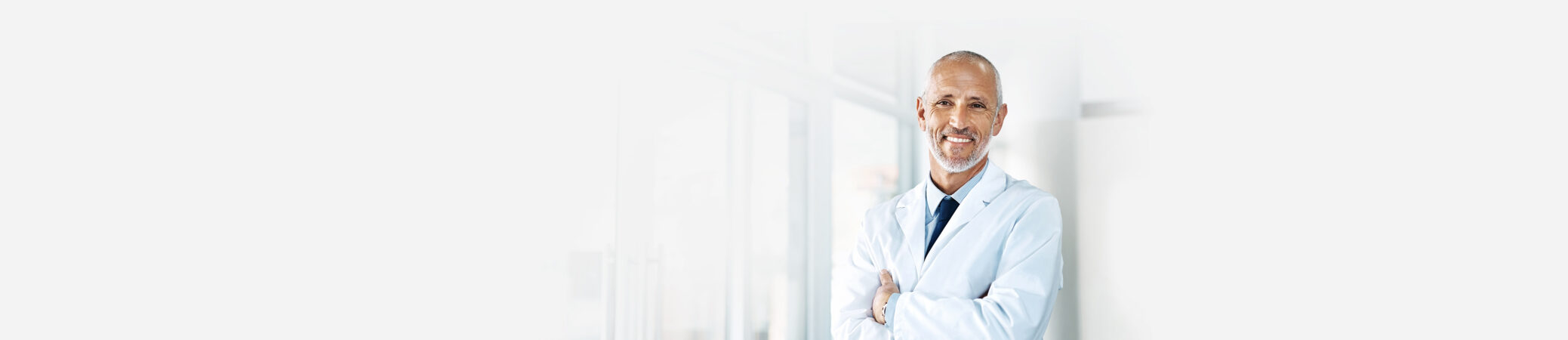 Doctor leaning against wall smiling