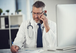 A doctor sitting talking on the phone