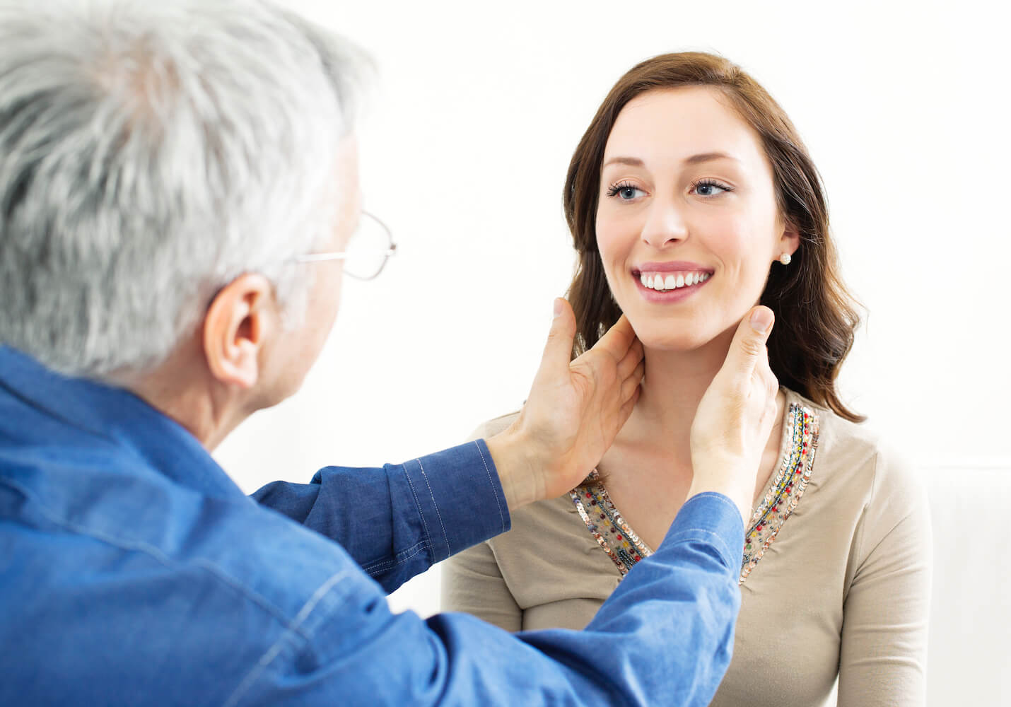 Doctor examining patient's thyroid