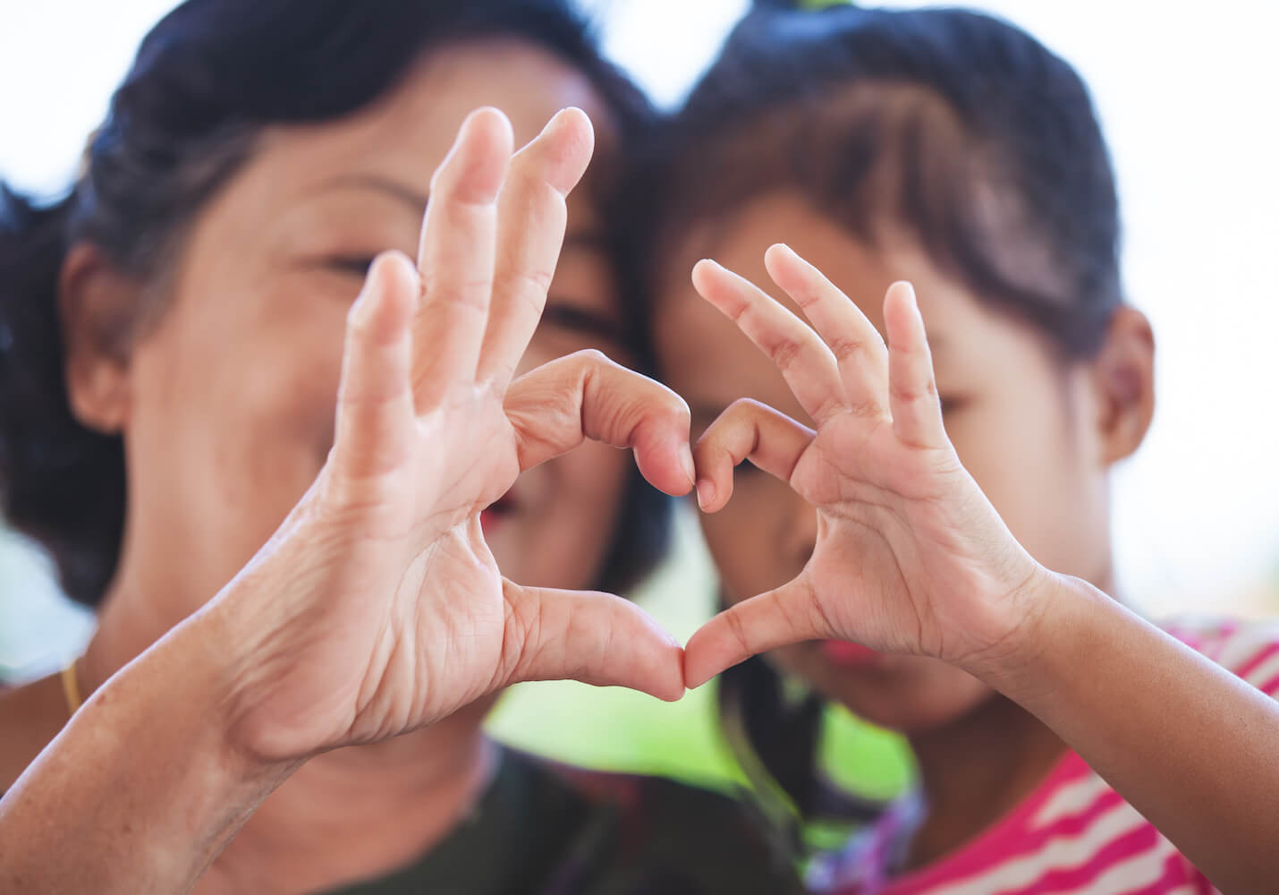 Woman and child making heart symbol