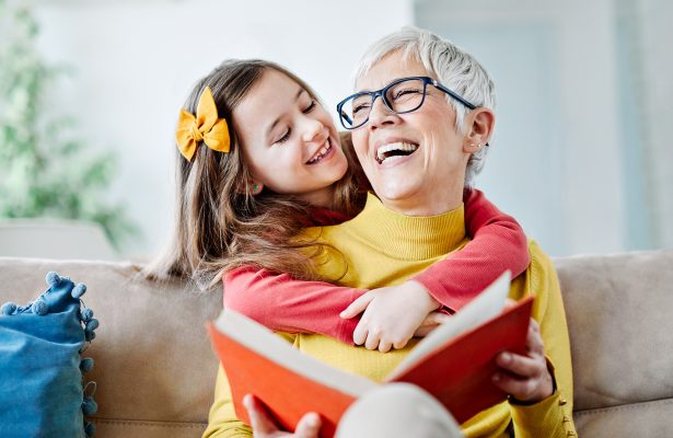A little girl laughs with and hugs her grandmother.