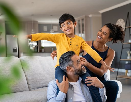 A boy smiles while playfully interacting with his mother and father.