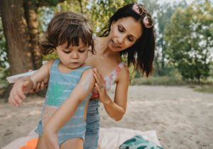 Mother applying sunscreen to child