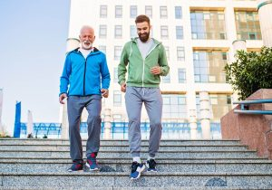 Older man and younger man exercising on stairs