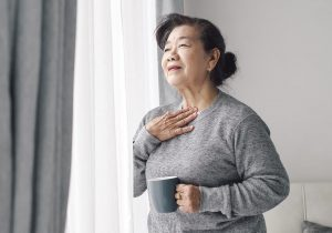 Senior woman nursing sore throat